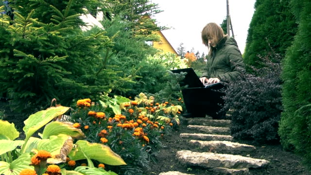 girl working with laptop in garden - wap stock videos & royalty-free footage