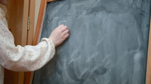 girl writing e=mc2 on blackboard - e=mc2 stock-videos und b-roll-filmmaterial