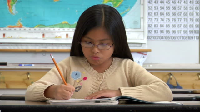 cu, girl (8-9) writing in classroom, portrait - straight hair stock videos & royalty-free footage