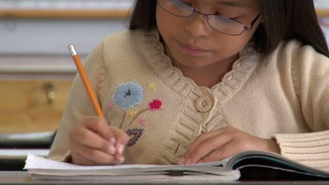 CU, Girl (8-9) writing in classroom, portrait