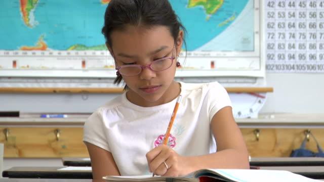 vídeos y material grabado en eventos de stock de cu, girl (8-9) writing in classroom, portrait - a la izquierda de