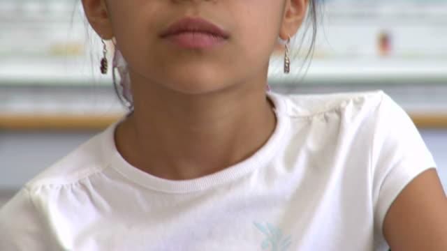 CU, TU, TD, Girl (8-9) writing in classroom, portrait