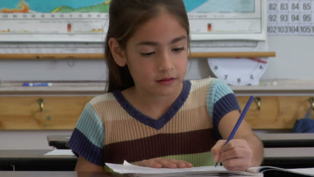 cu, girl (8-9) writing in notebook in classroom, portrait - video ritratto video stock e b–roll