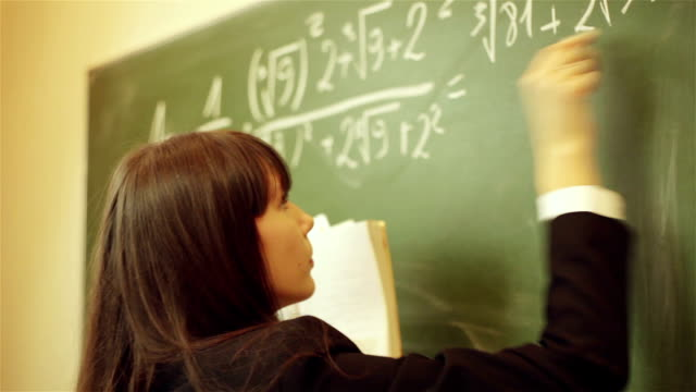 girl writing mathematical equation on chalkboard