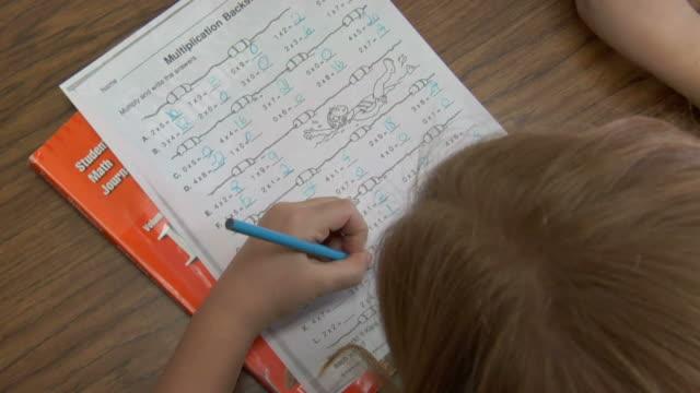 vídeos y material grabado en eventos de stock de cu, overhead view, girl (8-9) writing mathematics in classroom - a la izquierda de