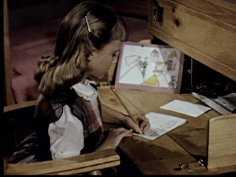 vidéos et rushes de ms, ha, girl (6-7) writing sitting at desk - écrire