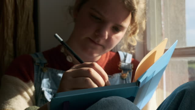 girl writing - note pad stock-videos und b-roll-filmmaterial