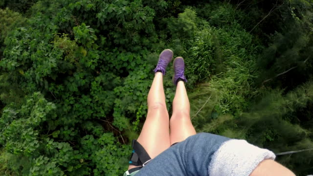 pov of girl ziplining over forest in hawaii - human leg stock videos & royalty-free footage