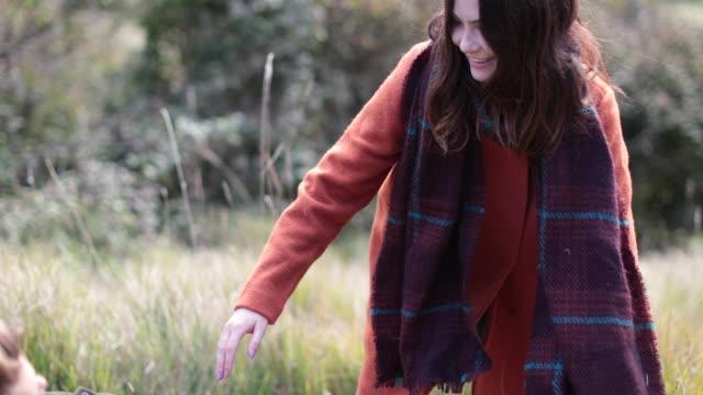 girlfriend helping boyfriend up in countryside - オーバーコート点の映像素材/bロール