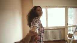 Girlfriend leading her boyfriend in their new house