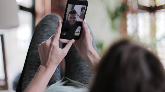 girlfriend on videocall to boyfriend - usare il telefono video stock e b–roll