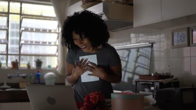 Petite amie recevant des fleurs de son petit ami et lui parlant sur Internet par l'intermédiaire de l'ordinateur portatif à la maison