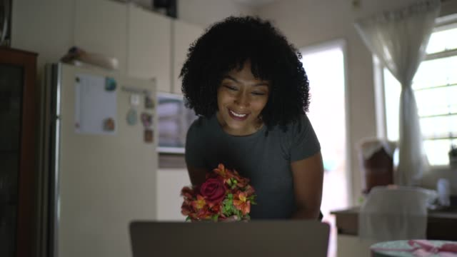 girlfriend receiving flowers / present of her boyfriend and talking to him on internet via laptop at home - long distance relationship stock videos & royalty-free footage