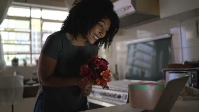 Petite amie recevant des fleurs / présent de son petit ami et lui parlant sur Internet via l'ordinateur portatif à la maison