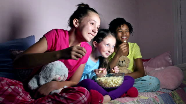 girlfriends at sleepover eating popcorn watching tv - pyjamas stock videos & royalty-free footage