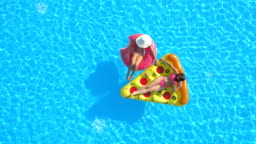 AERIAL Girlfriends enjoying on fun inflatable pizza and doughnut floats in pool