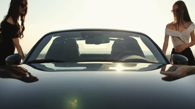 stockvideo's en b-roll-footage met vriendinnen het invoeren van een cabriolet op zonnige dag - sunny