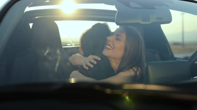 girlfriends flirting and hugging in car - convertible stock videos & royalty-free footage