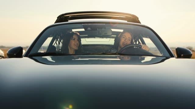 vídeos de stock, filmes e b-roll de amigas que flertam e que sorriem no carro - roupa descontraída