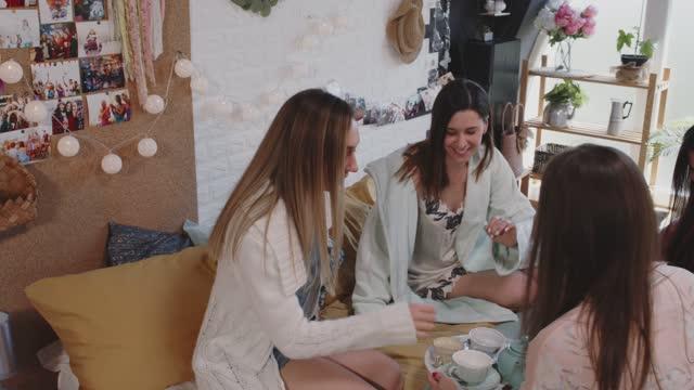 girlfriends gathering on bed to enjoy tea during sleepover - nightwear stock videos & royalty-free footage