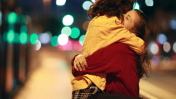 LGBT girlfriends getting married celebration, woman jumping into partner arms at night in the city