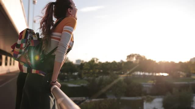 vídeos de stock e filmes b-roll de girlfriends hanging out on bridge at sunset - retroiluminado