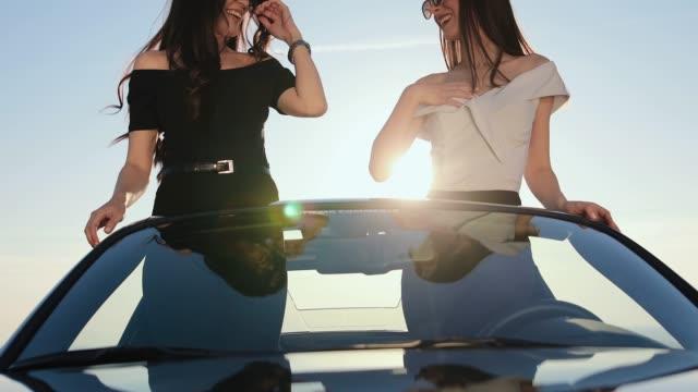 stockvideo's en b-roll-footage met vriendinnen plezier in cabriolet op zonnige dag - sunny