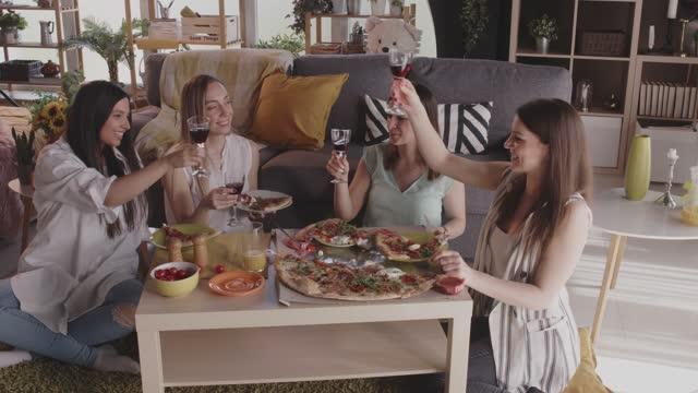 vídeos de stock e filmes b-roll de girlfriends making a celebratory toast before eating pizza - amizade feminina