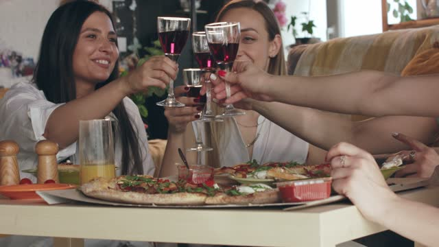 vídeos de stock e filmes b-roll de girlfriends making a celebratory toast with red wine while having pizza for lunch - amizade feminina
