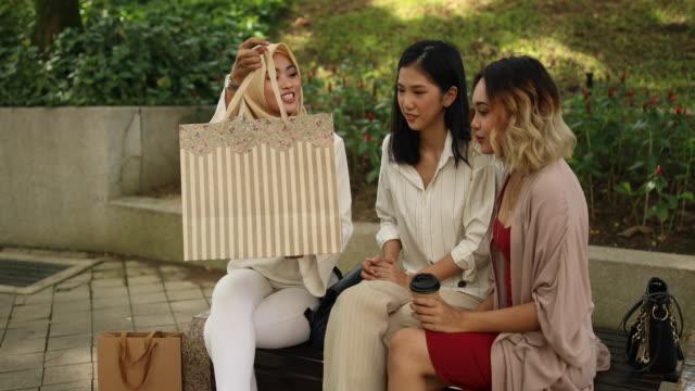 vídeos de stock, filmes e b-roll de namoradas relaxantes no parque depois das compras - vestuário modesto