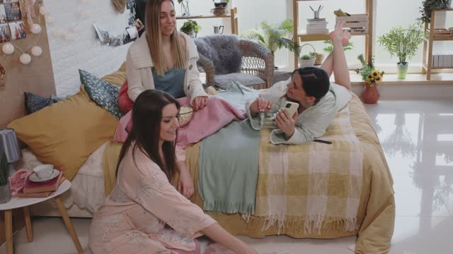 girlfriends relaxing on bed, snacking on popcorn and chatting during a sleepover - nightwear stock videos & royalty-free footage