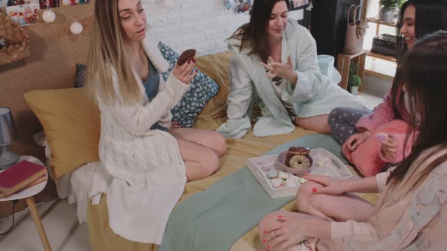 girlfriends sitting on bed and sharing sweet food and snacks - nightwear stock videos & royalty-free footage