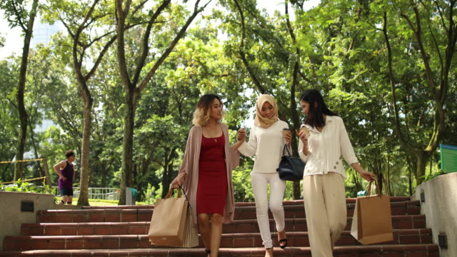 girlfriends walking down the park after shopping - kuala lumpur stock videos & royalty-free footage