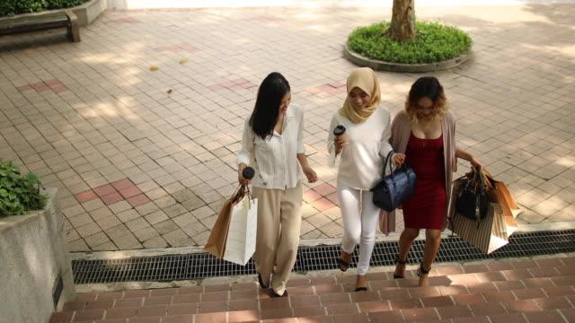 vídeos de stock, filmes e b-roll de namoradas, andando no parque depois das compras - vestuário modesto