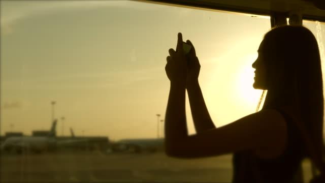mädchen benutzen mobiltelefone. fotografieren sie flugzeuge und start- und landebahnen, silhouette style. - flugpassagier stock-videos und b-roll-filmmaterial
