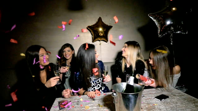 Girls at a party popping confetti