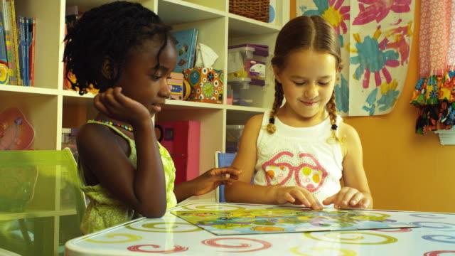 MS Girls (4-5) at activity table finish up Puzzle / Burbank, California, USA