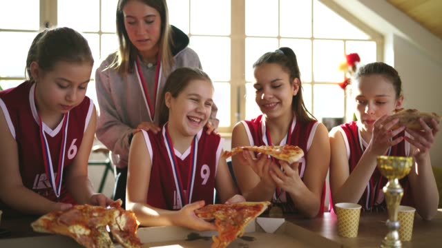 girls basketball players eating pizza with coach after winning a trophy - unhealthy eating stock videos & royalty-free footage