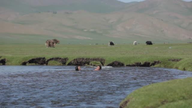 girls bathing in the river with animals and mountains on the background - liten djurflock bildbanksvideor och videomaterial från bakom kulisserna