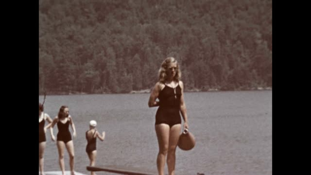 a girls camp on lake schroon in the adirondacks in the 1940's the girls are having a race doing the backstroke while holding a newspaper - summer camp helper stock videos & royalty-free footage