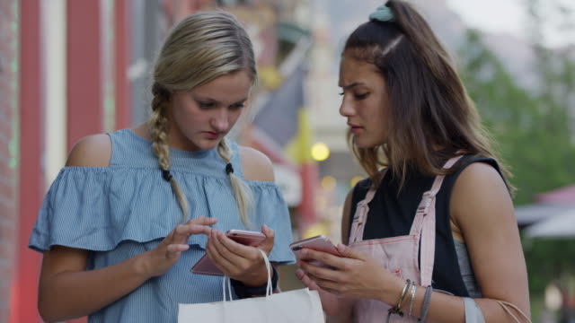 girls carrying shopping bags in city texting on cell phones / provo, utah, united states - provo stock videos & royalty-free footage