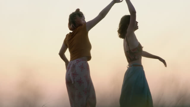 ws slo mo. girls dancing in flowing dresses in summer wheat field at magic hour. - togetherness stock videos & royalty-free footage