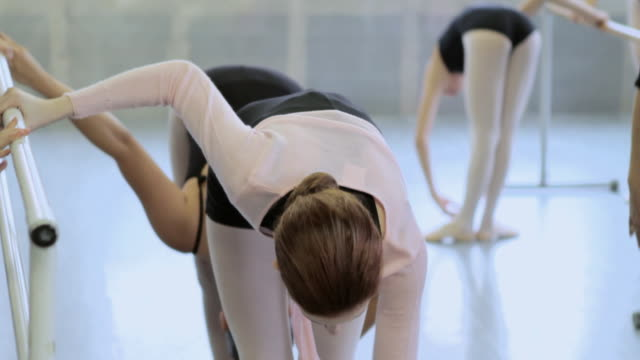 Girls doing ballet exercises at barre, teacher helping
