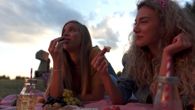 vídeos de stock, filmes e b-roll de meninas que comem seus petiscos do piquenique - comida doce