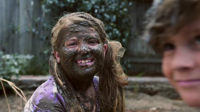 vídeos de stock e filmes b-roll de girls face covered in mud - cu coverage - lama solo