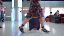 Girl's feet walking with luggage in airport.