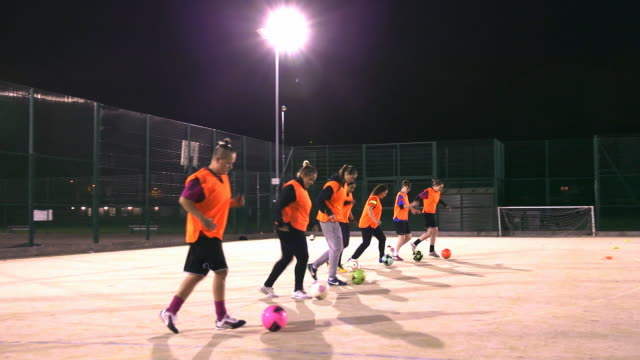 a girls football team practise dribbling in a line during training. - endurance stock videos & royalty-free footage