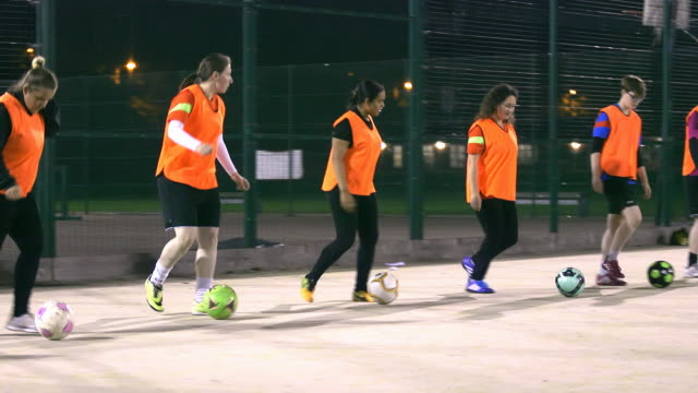 a girls football team practise dribbling in a line during training. - genderblend stock videos & royalty-free footage
