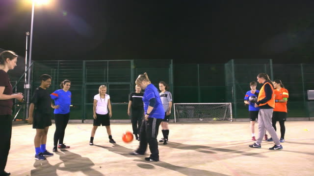 A girls football team practise headers and volleys during training