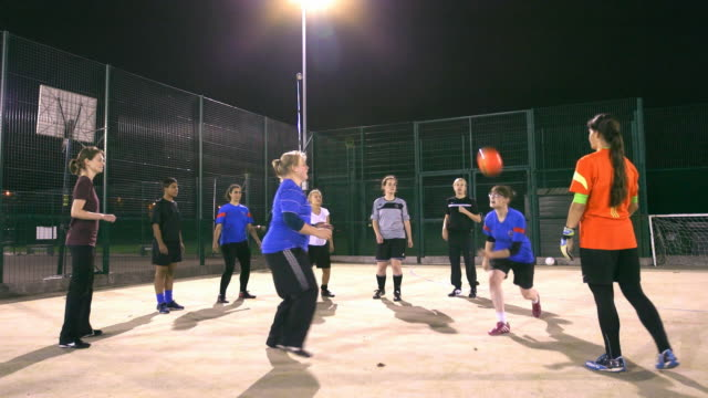 a girls football team practise headers and volleys during training - genderblend stock videos & royalty-free footage